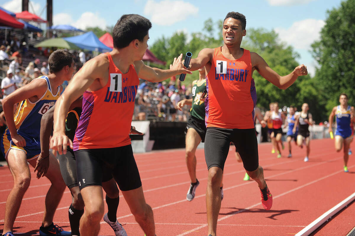 Danbury High's Trevor Reed passes the baton to Pedro Pereira during their win in the 4 x 800 relay at the State Open track championships at New Britain Stadium in New Britain, Conn. on Monday, June 6, 2016.