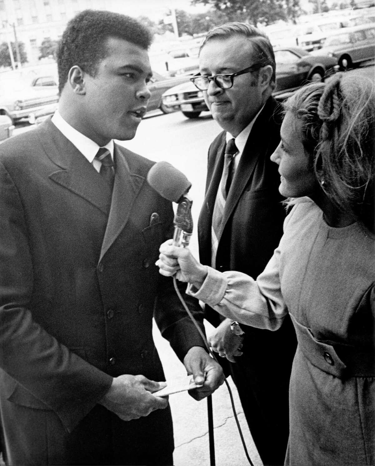 Ali is interviewed by KPRC-TV news reporter Kay Bailey as his attorney Charles Morgan Jr. looks on in downtown Houston on Aug. 3, 1969.