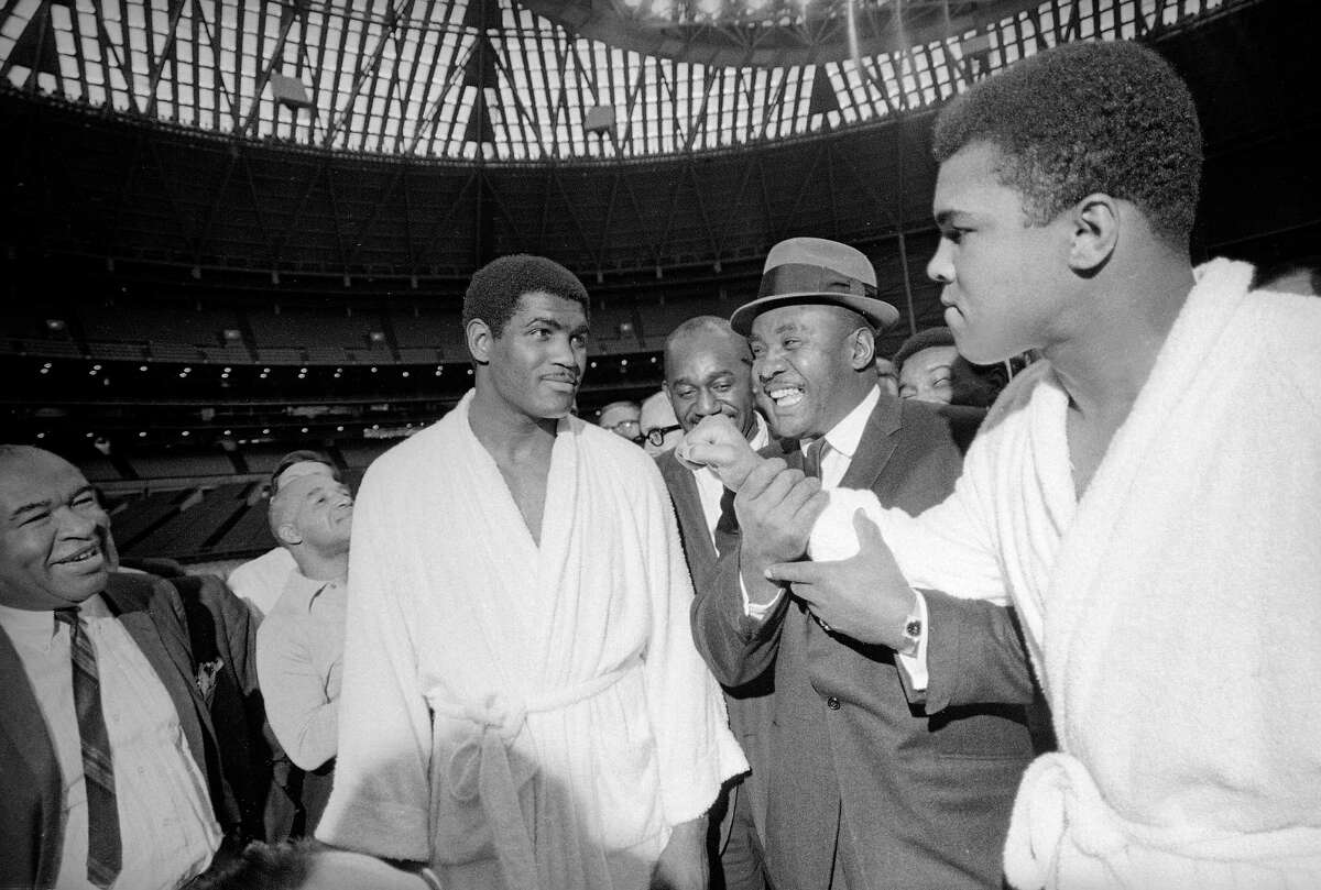 Muhammad Ali playfully throws a punch in the direction of Ernie Terrell as former heavyweight champion Sonny Liston, center, joins in the fun at a prefight medical exam in Houston on Feb. 1, 1967.