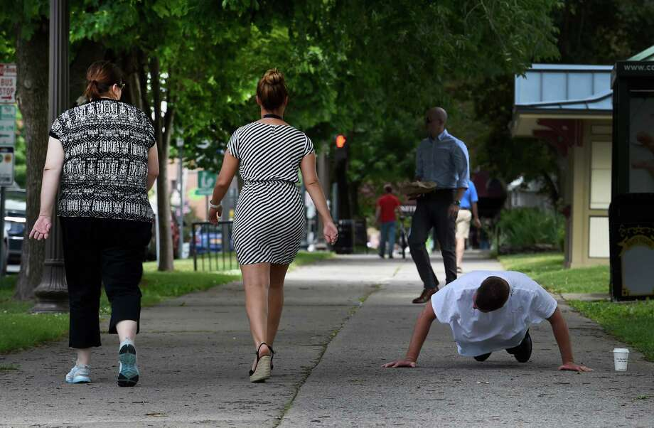 A man does some exercises on lower Broadway as pedestrians walk by on Monday, June 6, 2016, in Saratoga Springs, N.Y. (Skip Dickstein/Times Union) Photo: SKIP DICKSTEIN / 40036860A