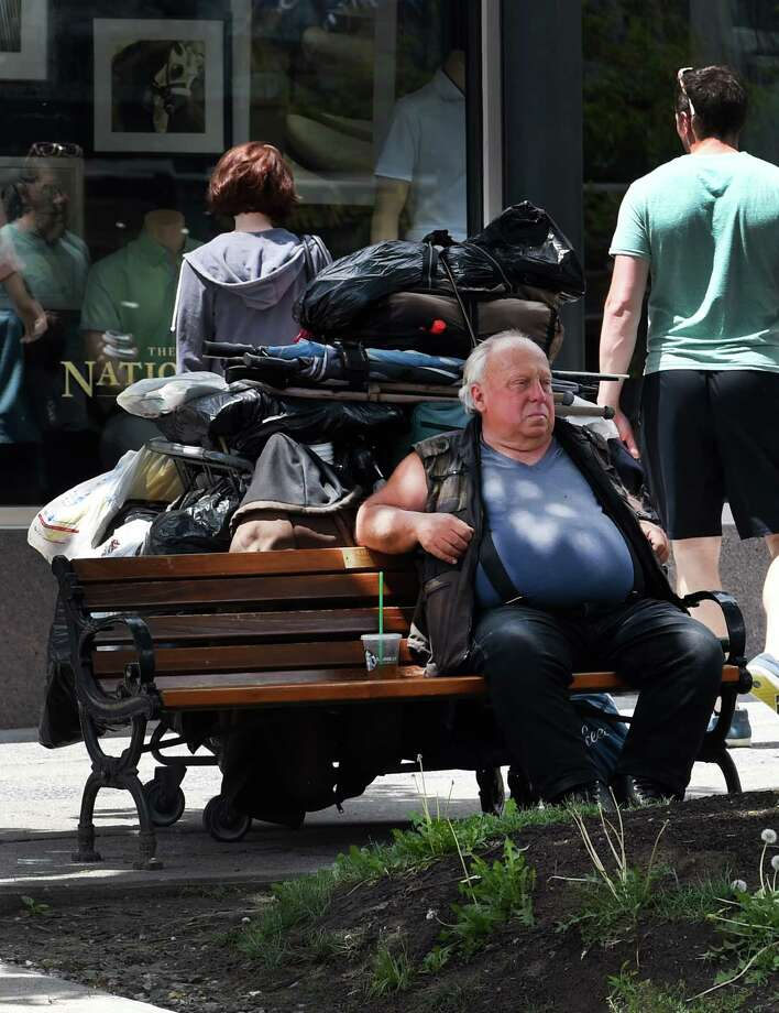A man sits on a bench on Broadway as pedestrians walk by Monday, June 6, 2016, in Saratoga Springs, N.Y. (Skip Dickstein/Times Union) Photo: SKIP DICKSTEIN / 40036860A