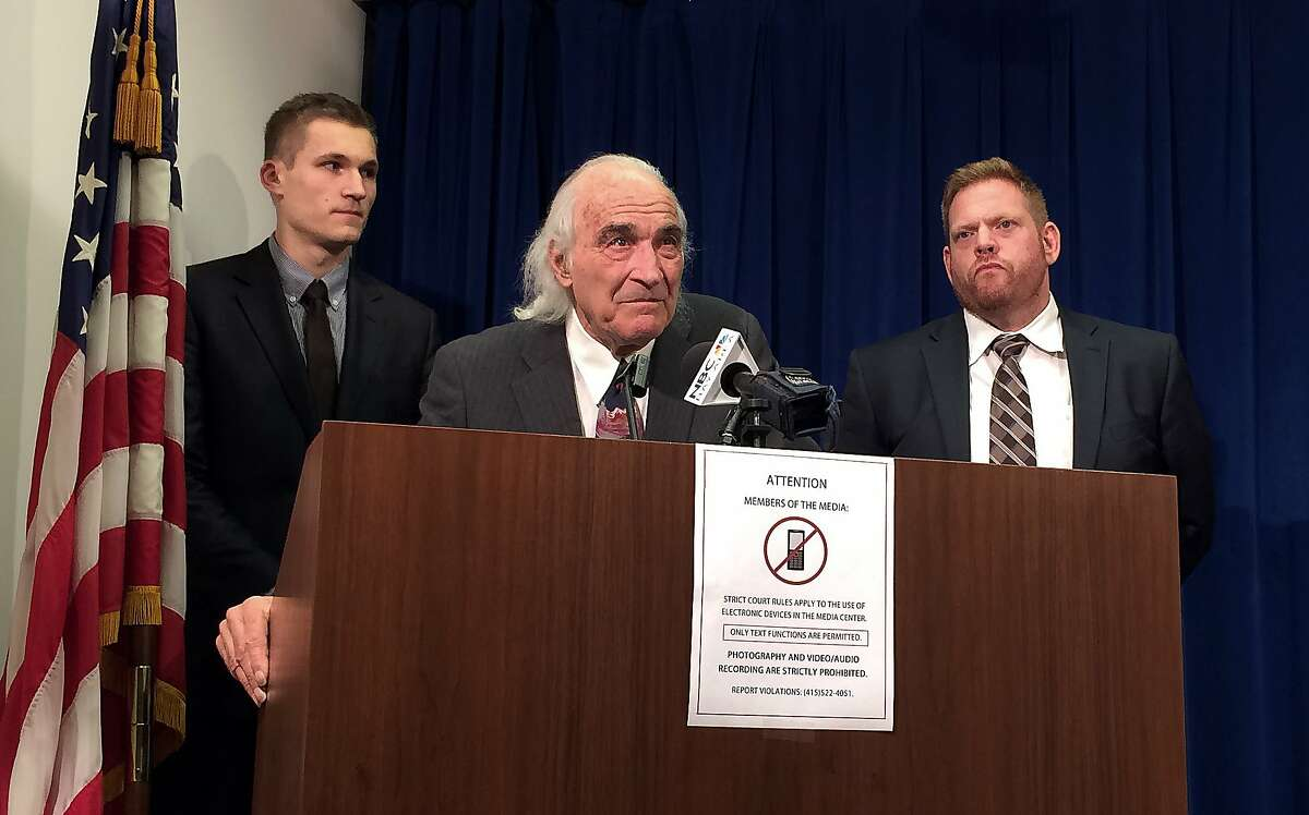 """J. Tony Serra, lead attorney for Raymond """"Shrimp Boy"""" Chow, center, speaks to reporters Tuesday, Jan. 5, 2016, at the Phillip Burton Federal Building in San Francisco. The trial of Chow, a man charged with murder and racketeering in an organized crime investigation centered in San Francisco's Chinatown is headed to a jury. Prosecutors have said Chow took over a Chinese fraternal group with criminal ties after having its previous leader killed and ran an enterprise that engaged in drug trafficking, money laundering and the sale of stolen cigarettes and alcohol. He also is charged with conspiring to kill another gang rival. Defense attorney Curtis Briggs is seen at right, and student intern Patrick Stefek on left. (AP Photo/Janie Har)"""