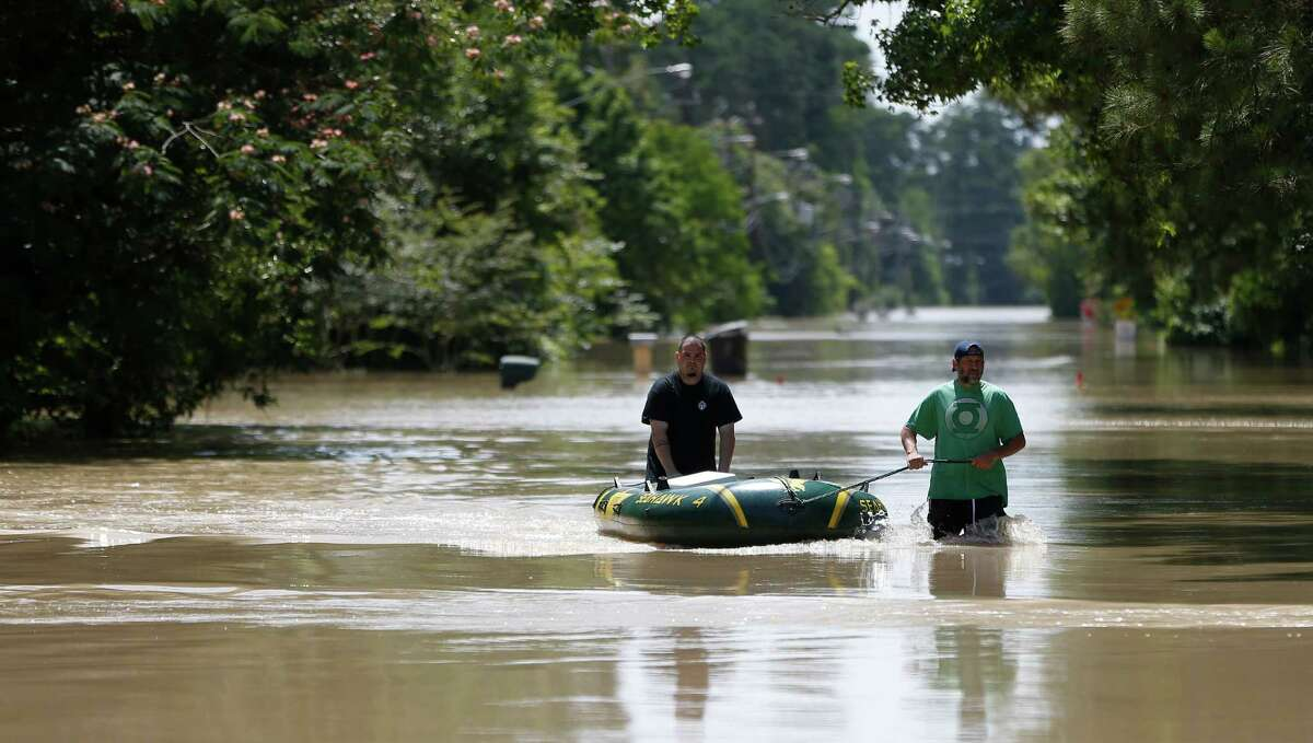 Thomas Wirtjes, left, and Tad Gibson, right, use a rubber boat on Hamblen Road, to bring back supplies to their homes surrounded by flood waters in the Forest Cove neighborhood, south of Kingwood, where flood waters from the San Jacinto Rivers reached levels not seen since 1994, Sunday, May 29, 2016, in Humble. ( Karen Warren / Houston Chronicle )