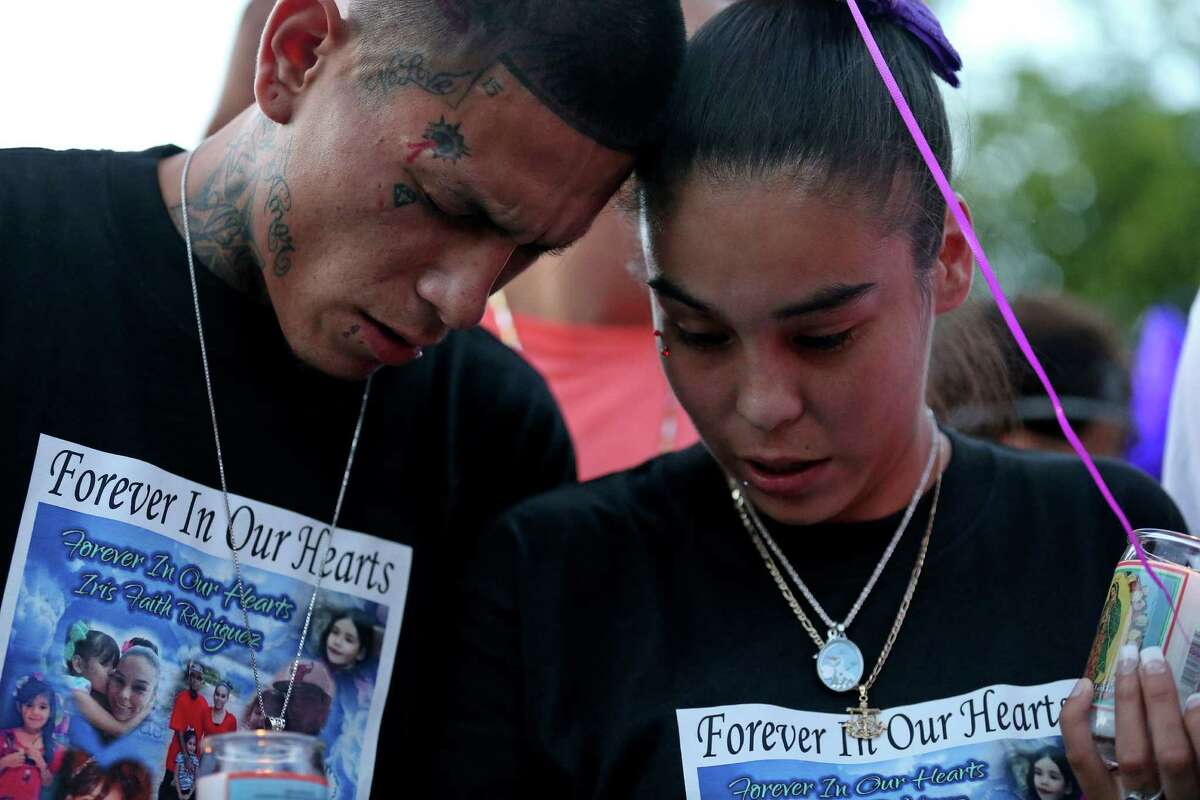 Victor Badillo (left), his wife Eva Juarez, and others pray during a candlelight vigil held Monday June 6, 2016 in remembrance of their 7-year-old daughter Iris Rodriguez who was fatally shot in the 5500 block of San Fernando Street Wednesday June 1, 2016 and died at University Hospital Thursday evening. About 200 people attended the vigil.