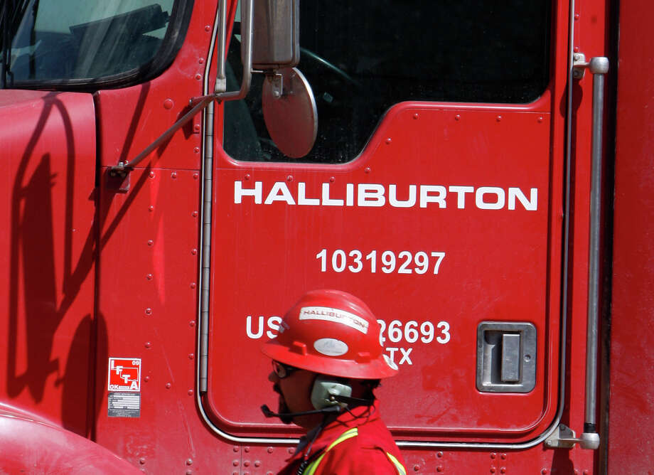 FILE - In this April 15, 2009, file photo, an unidentified worker passes a truck owned by Halliburton at a remote site for natural-gas producer Williams in Rulison, Colo. (AP Photo/David Zalubowski, File) Photo: David Zalubowski, STF / AP