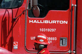 FILE - In this April 15, 2009, file photo, an unidentified worker passes a truck owned by Halliburton at a remote site for natural-gas producer Williams in Rulison, Colo. Halliburton Co., which provides well-drilling services for oil companies, is cutting 5,000 more jobs as the industry continues to struggle with slumping oil prices, the company announced Thursday, Feb. 25, 2016. (AP Photo/David Zalubowski, File)