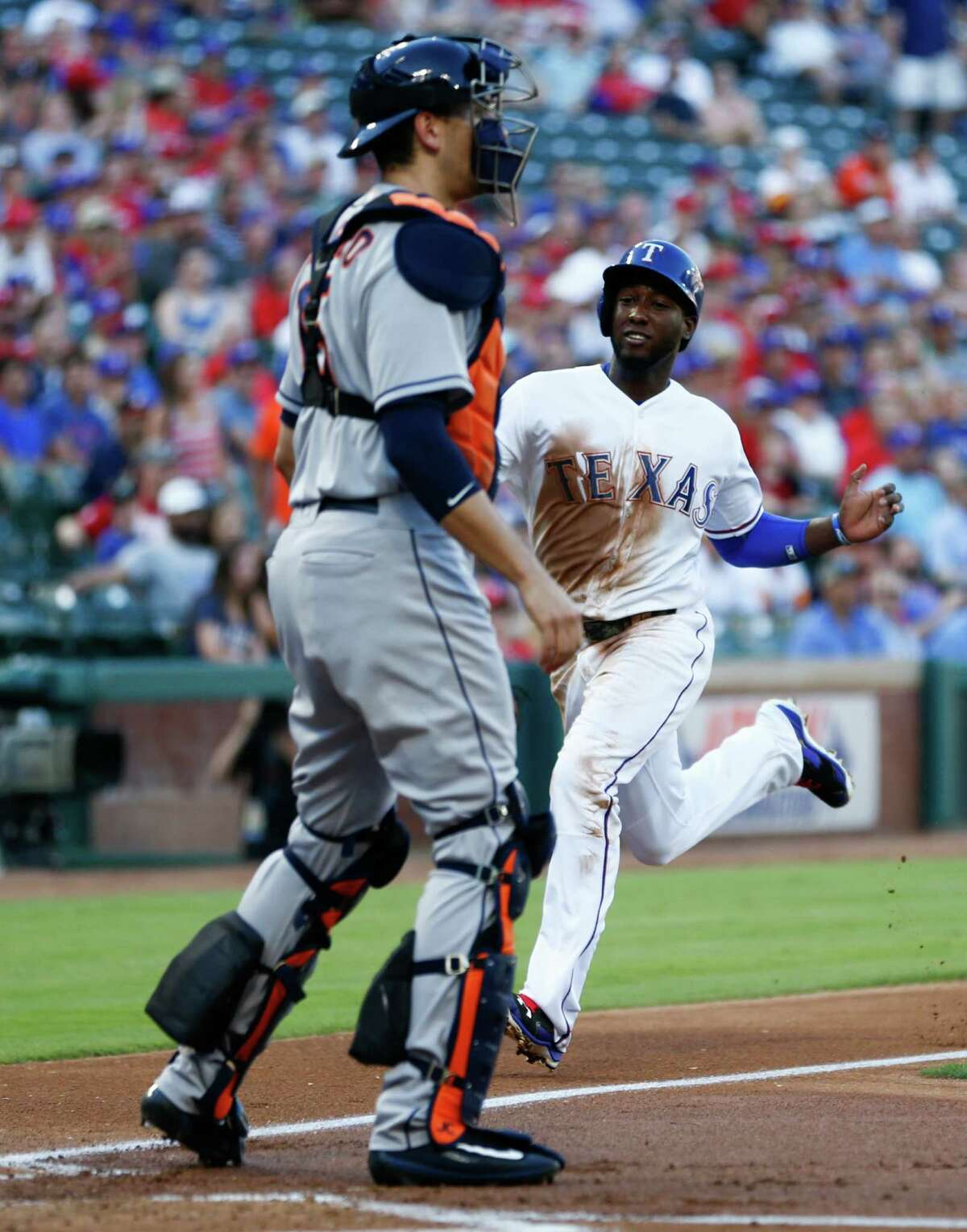 Texas Rangers second baseman Jurickson Profar, right, scores on a single by Ian Desmond in front of Houston Astros catcher Jason Castro during the first inning on Monday, June 6, 2016, at Globe Life Park in Arlington, Texas.