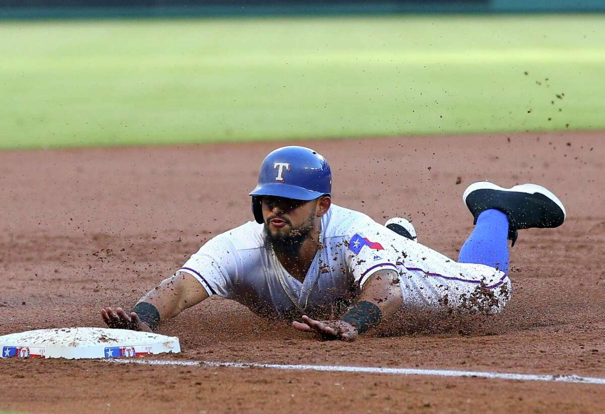 ARLINGTON, TX - JUNE 06: Rougned Odor #12 of the Texas Rangers slide in safe to third base in the first inning against the Houston Astros at Globe Life Park in Arlington on June 6, 2016 in Arlington, Texas.