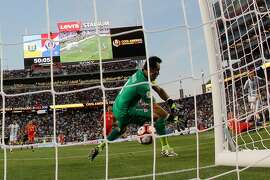 Argentina�s Angel Di Maria, right, scores past Chile�s goalkeeper Claudio Bravo, left, during a Copa America Centenario Group A soccer match at the Levi's Stadium in Santa Clara, Calif., Monday, June 6, 2016. Argentina defeated Chile 2-1. (AP Photo/ Marcio Jose Sanchez)