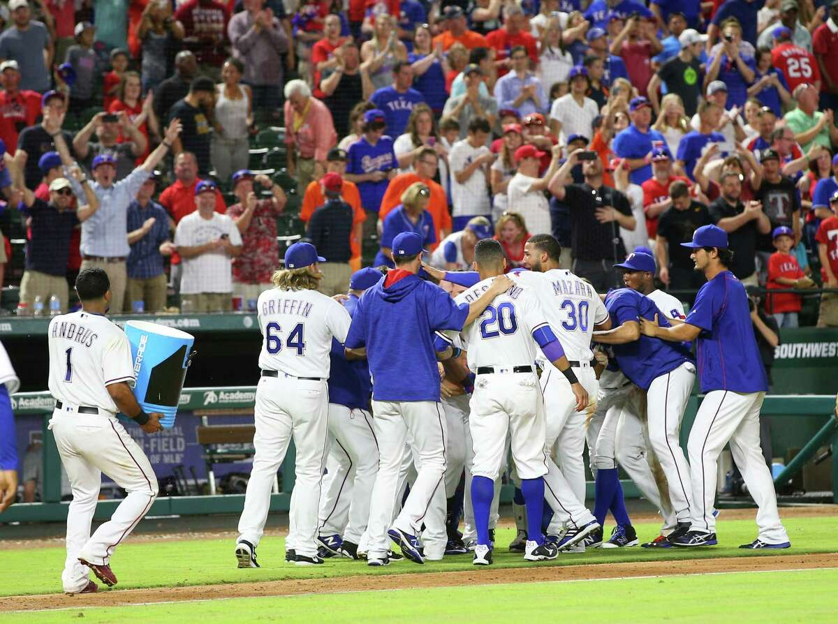 June 6: Rangers 6, Astros 5 ARLINGTON, TX - JUNE 06: Elvis Andrus #1 of the Texas Rangers carries the cooler while A.J. Griffin #64, Ian Desmond #20, Nomar Mazara #30, Yu Darvish #11 and the team celebrate Rougned Odor hitting a double in the ninth inning for Adrian Beltre to make the winning run against the Houston Astros at Globe Life Park in Arlington on June 6, 2016 in Arlington, Texas.