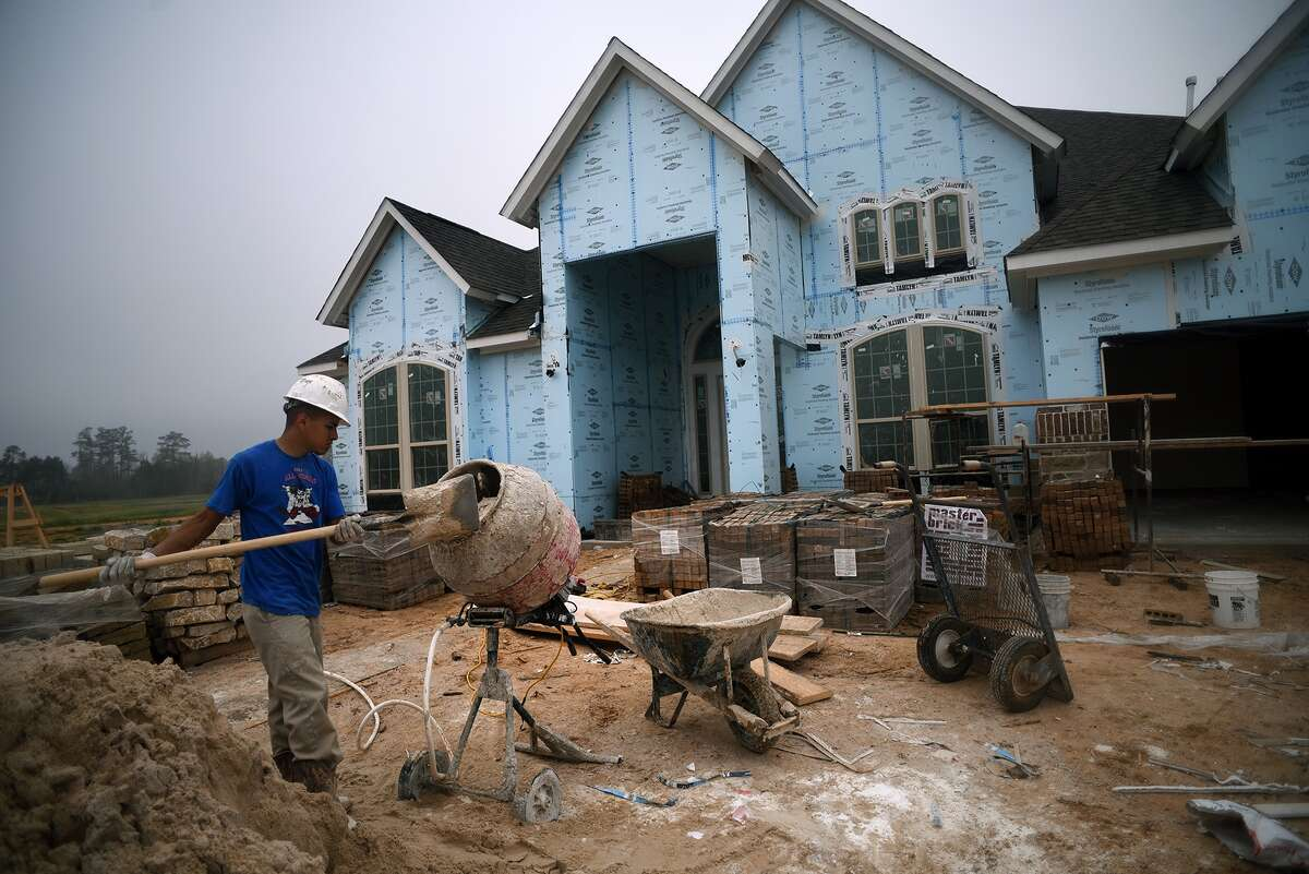 A worker mixes a batch of mortar for brickwork at a home under construction in the Lakes at Creekside community in Tomball.
