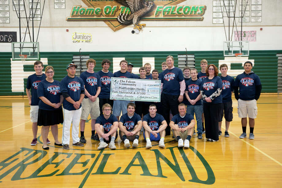Kevin Townsend, left of check, Freeland High School varsity football head coach, along with his team, recently presented a $5,000 donation to Greg Rogers, right of check, president of MidMichigan Medical Center-Midland. Also representing MidMichigan for the check presentation was Denise O'Keefe, end of second row on the left, director of fund development for MidMichigan Health, and Joan Herbert, end of second row on the right, director of oncology services for MidMichigan Health. Proceeds were raised during the annual Clash for a Cure football game last fall. Since the event started in 2010, the school has donated $57,000 to MidMichigan's Cancer Fund. This fund provides support for technology, education, special patient care items and services to support the emotional, physical and financial challenges of those fighting cancer.