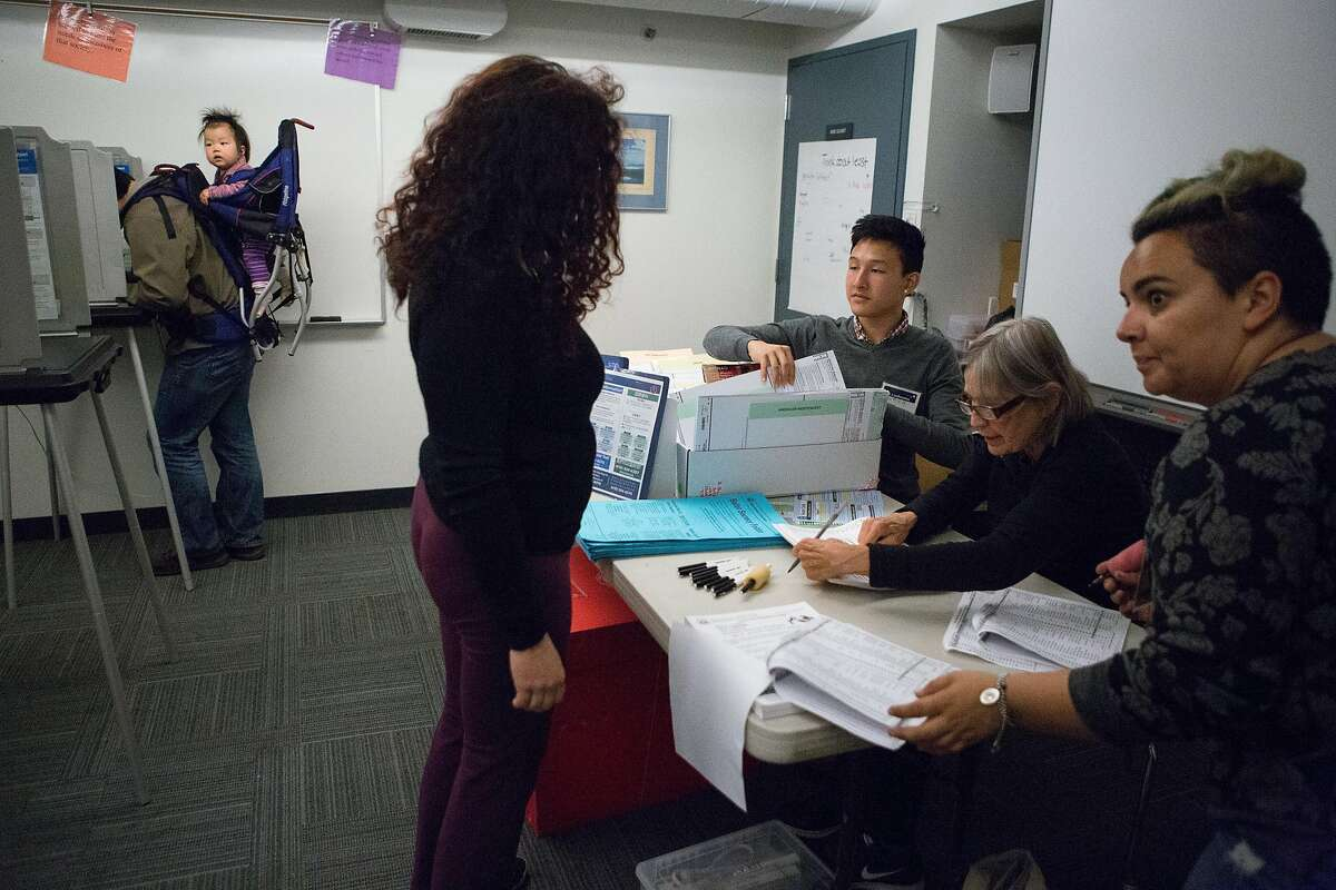 (Left to Right) Maya Lincoln, 1, watches the action as voter Rebecca Robbins receives her ballot from poll workers Matthew Lee, Katherine Wright, and Jenna Lester, at a polling location on Page Street in the Haight, San Francisco on Tuesday, June 7, 2016.