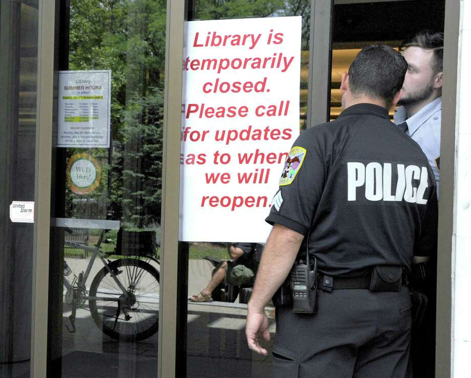 Sgt. Jim Antonelli talks to a security guard through the door of the Danbury Library, temporarily closed Tuesday afternoon, June 7, 2016, after a man was arrested for causing a disturbance in the building. Photo: Carol Kaliff / Hearst Connecticut Media / The News-Times