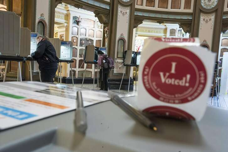 """An """"I Voted"""" sticker sits on a table as residents make selections on their ballots while voting in the San Francisco Columbarium polling location during the presidential primary election in San Francisco, California, U.S., on Tuesday, June 7, 2016. Hillary Clinton secured the delegates required to claim the Democratic presidential nomination Monday, putting further pressure on Bernie Sanders to exit the race. Photographer: David Paul Morris/Bloomberg"""