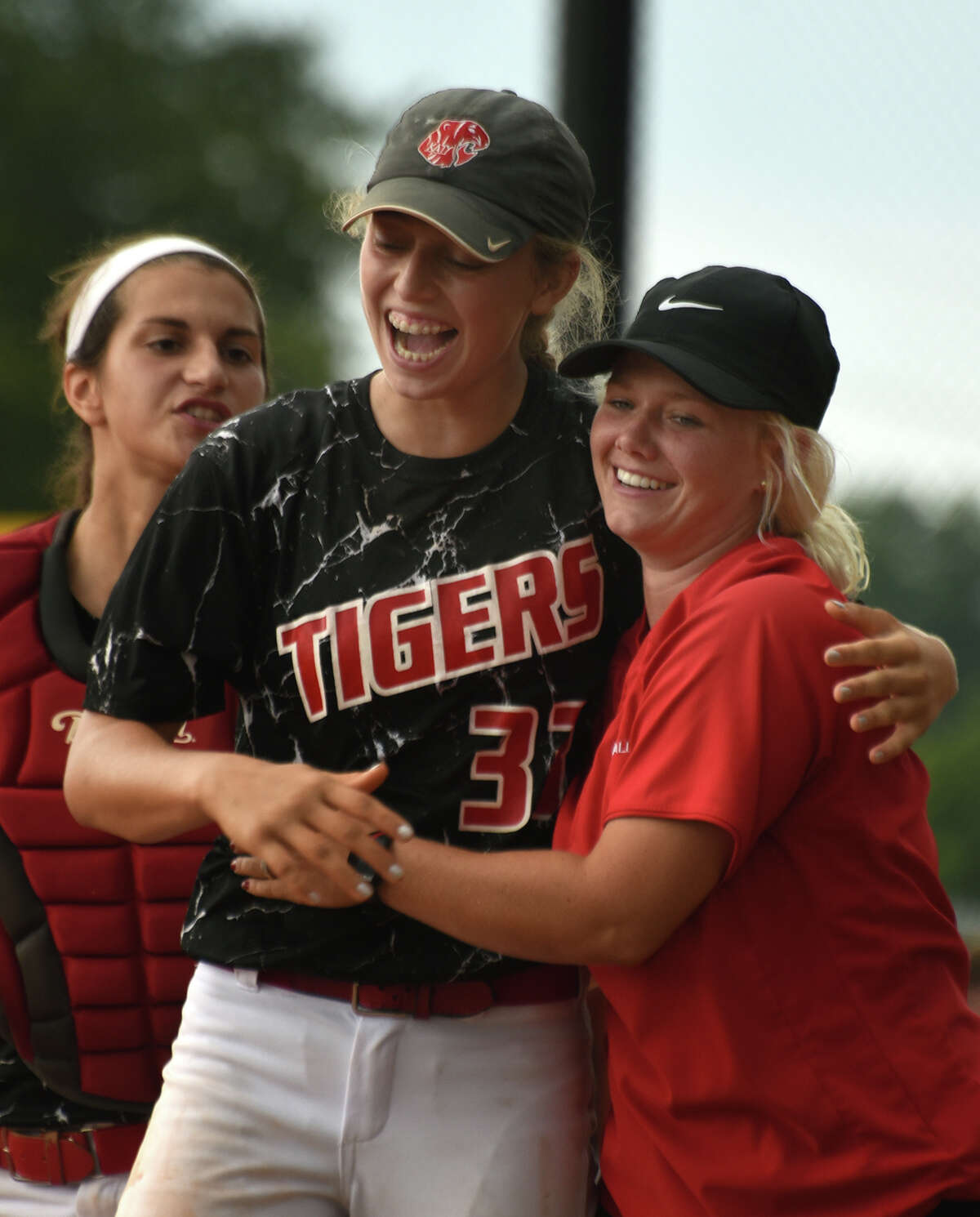Katy junior pitcher Kylie Redding, center, gets a hug from acting head coach Meghan Brown after finishing game 3 of the Tiger's Region III-6A semifinal playoff series matchup against Alvin at Katy High School on May 21, 2016. (Photo by Jerry Baker/Freelance)