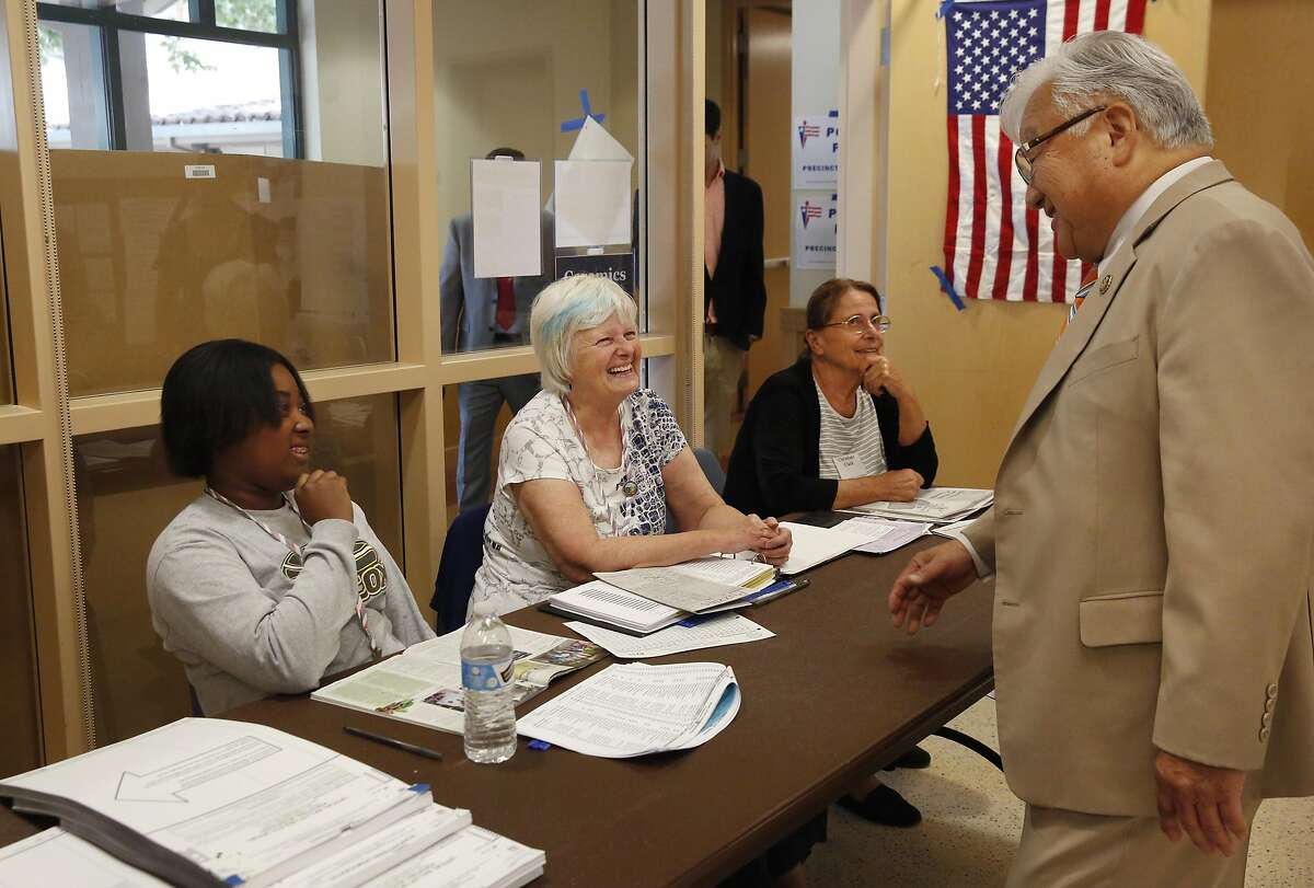 U.S. Representative Mike Honda, right, greets Election Officials, from left, Shelby Bennett, Judy Tucker and Christiane Clark at a polling place in the City of Santa Clara Senior Center June 7, 2016 in San Jose, Calif.