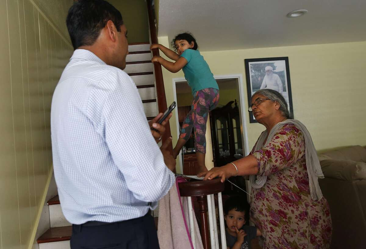 Congressional candidate Ro Khanna, left, chats in Hindu with Lakwander Kaur, right, as her grand children Manreet Kaur, 5, upper center, and Sahib Singh, 2, watch as Khanna canvasses a neighborhood before polls close June 7, 2016 in San Jose, Calif.