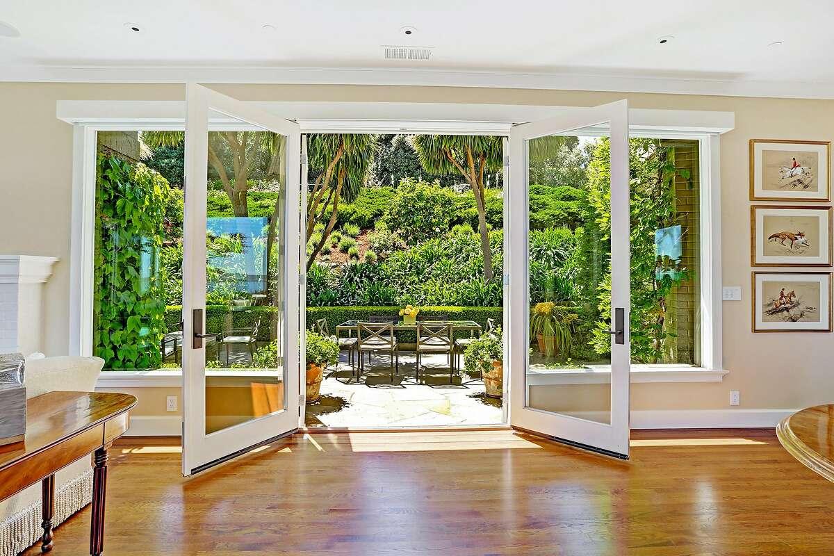 Double doors open to a slate patio beside terraced gardens.