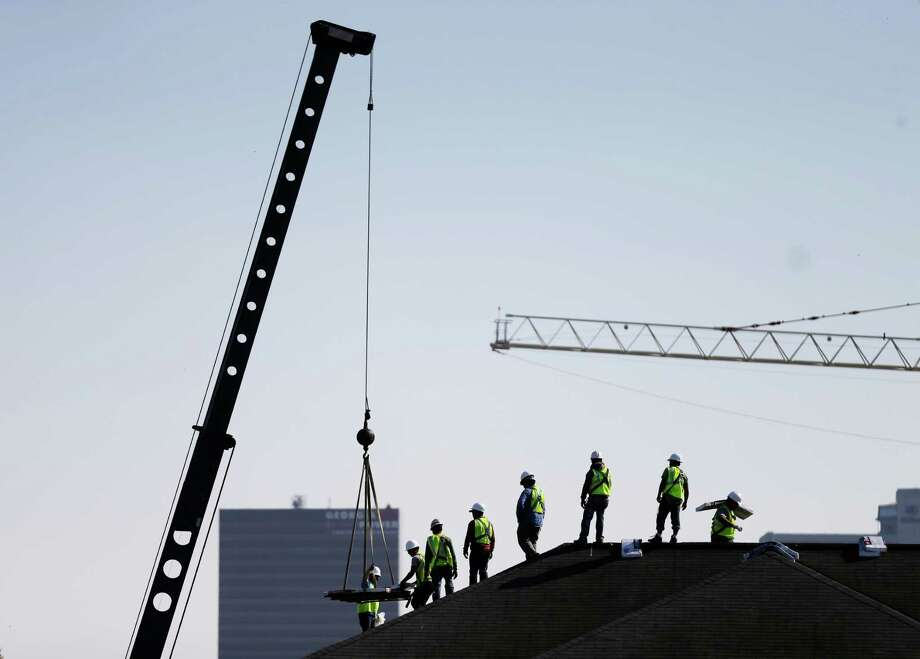 Construction workers unload supplies on a rooftop in Atlanta this spring. Photo: David Goldman, STF / Copyright 2016 The Associated Press. All rights reserved. This material may not be published, broadcast, rewritten or redistribu