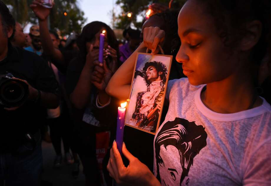 (FILES) This file photo taken on April 21, 2016 shows  People attending a candlelight vigil for pop music icon Prince, April 21, 2016 at Leimert Park in Los Angeles, California.   Prince died from an overdose of painkillers, a report said on June 2, 2016, quoting the ongoing investigation. The Star Tribune newspaper in Prince's hometown Minneapolis quoted an anonymous source as saying that the singer had overdosed on opioid pain medication. Officials declined comment.  / AFP PHOTO / ROBYN BECKROBYN BECK/AFP/Getty Images Photo: ROBYN BECK, AFP/Getty Images
