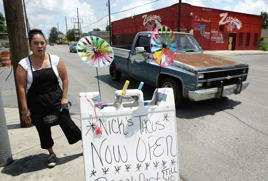 Regina Navarro, co-owner of Nick's Taco Catering on Zarzamora St., sets up a sidewalk menu which is across the street from Zarzamora Street Gym on Tuesday, June 7, 2016.  A mediation agreement approved last month in Kerr County calls for Jenna Lewis, Tony Ayala's common-law wife, to get the Zarzamora Street Gym and to pay Pauline Ayala, his mother $45,000 within one year. Photo: Bob Owen, Staff / San Antonio Express-News / ©2016 San Antonio Express-News