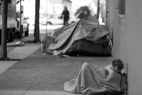 Daniel Pledger rests against a building on Florida Street as he sits under  blankets covering him on Friday, April 29, 2016 in San Francisco, California.  Pledger says he's been homeless since last August.