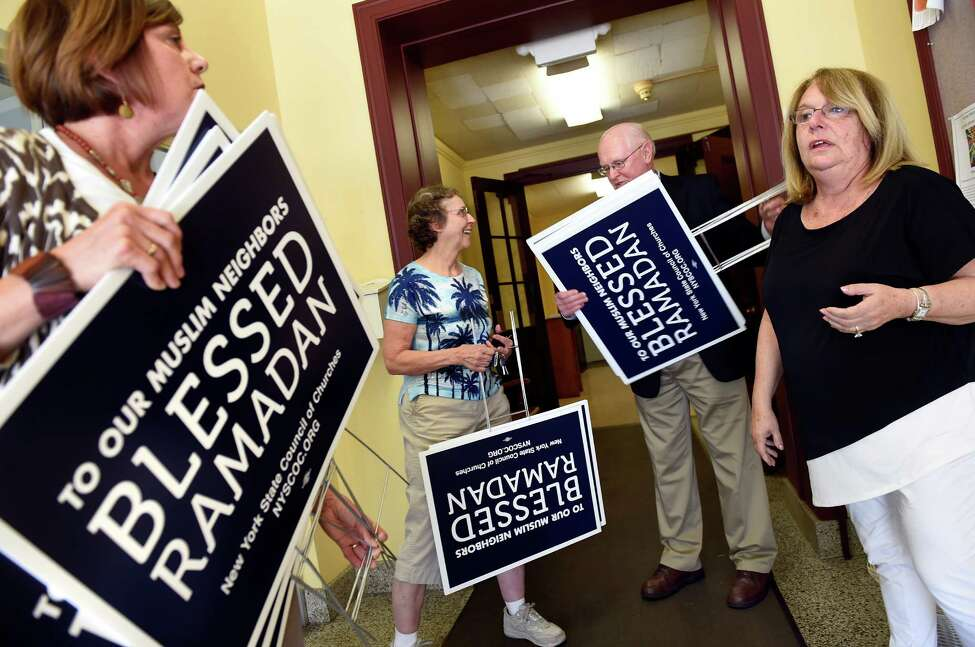 Deb Riitano, executive director of Capital Area Council of Churches, right, sells Ramadan signs to church groups on Tuesday, June 7, 2016, at First Lutheran Church in Albany, N.Y. From left are Angela Warner of St. Vincent de Paul, Lois Caulfield of Delmar Reformed Church and Deacon Walter Ayres of Catholic Charities. (Cindy Schultz / Times Union)