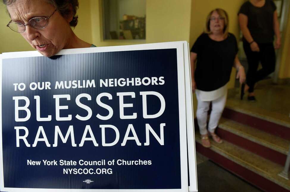 Lois Caulfield of Delmar Reformed Church, left, carries out Ramadan signs she bought from Deb Riitano, executive director of Capital Area Council of Churches, center, on Tuesday, June 7, 2016, at First Lutheran Church in Albany, N.Y. (Cindy Schultz / Times Union)