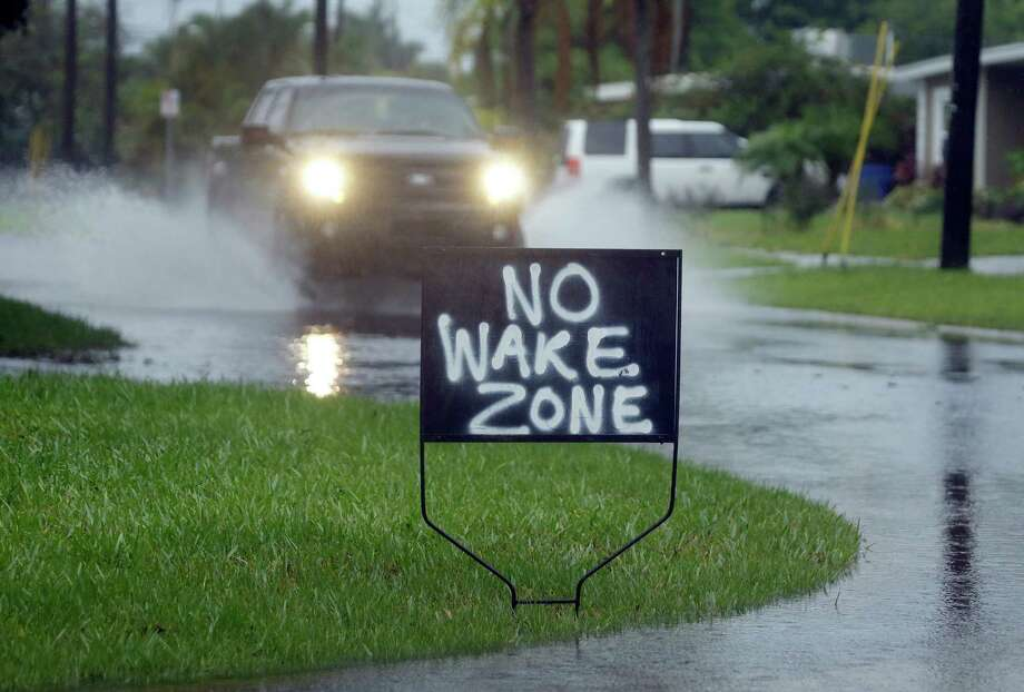 A resident of Shore Acres in St. Petersburg, Fla., has a sign urging motorists to slow down on flooded streets on Tuesday. Remnants of Tropical Storm Colin continued to dump rain along Florida's Gulf Coast. Photo: Chris O'Meara, STF / Copyright 2016 The Associated Press. All rights reserved. This material may not be published, broadcast, rewritten or redistribu