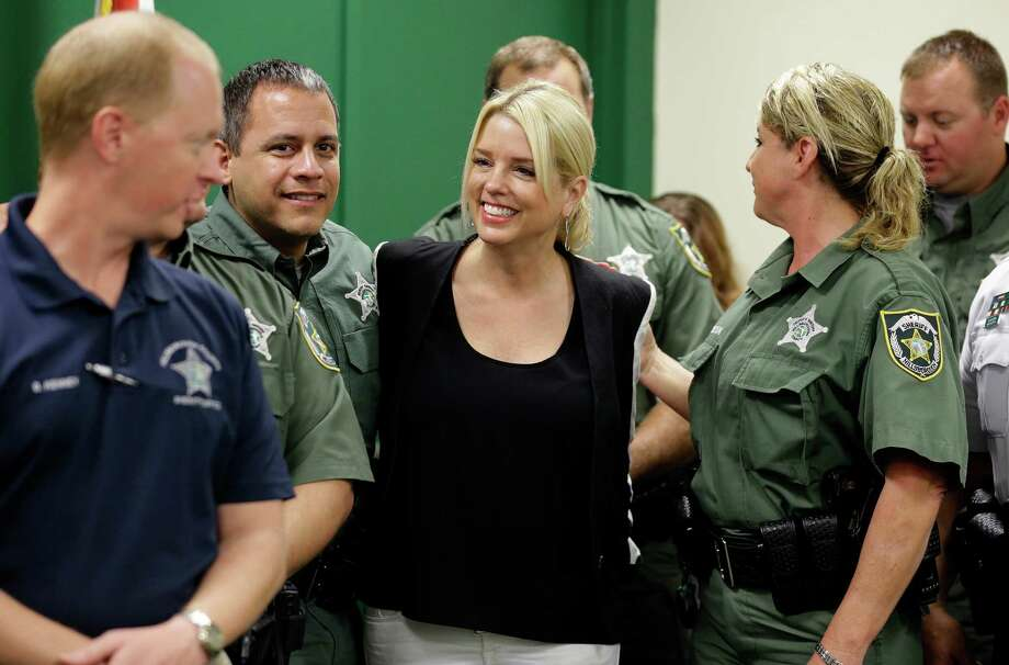 Florida Attorney General Pam Bondi, center, has come under fire for taking a $25,000 donation from Donald Trump's charitable foundation as her office weighed whether to join a lawsuit against Trump University. Photo: Chris O'Meara, STF / AP
