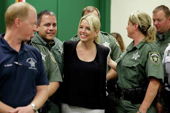 Florida Attorney General Pam Bondi, center, has come under fire for taking a $25,000 donation from Donald Trump's charitable foundation as her office weighed whether to join a lawsuit against Trump University.