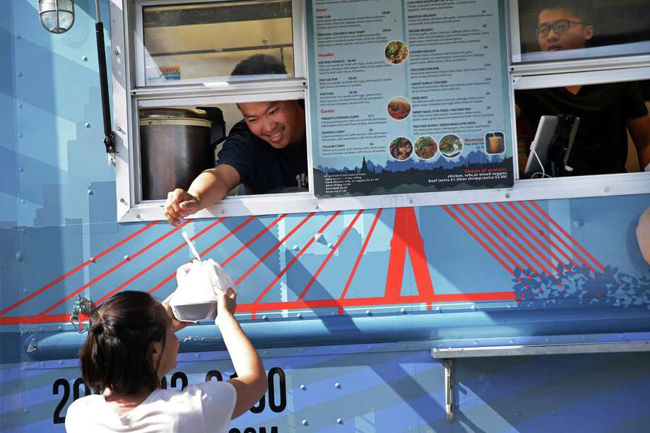 Take a look at some of Seattle's best-named food trucks. Above, Ferry Ijaya hands an order out the window of the Thai-U-Up food truck to Kylie Knowles on Tuesday.  Knowles is a frequent patron of the truck; her go-to dish is the Veggie Delight. Photo: GENNA MARTIN, SEATTLEPI.COM / SEATTLEPI.COM