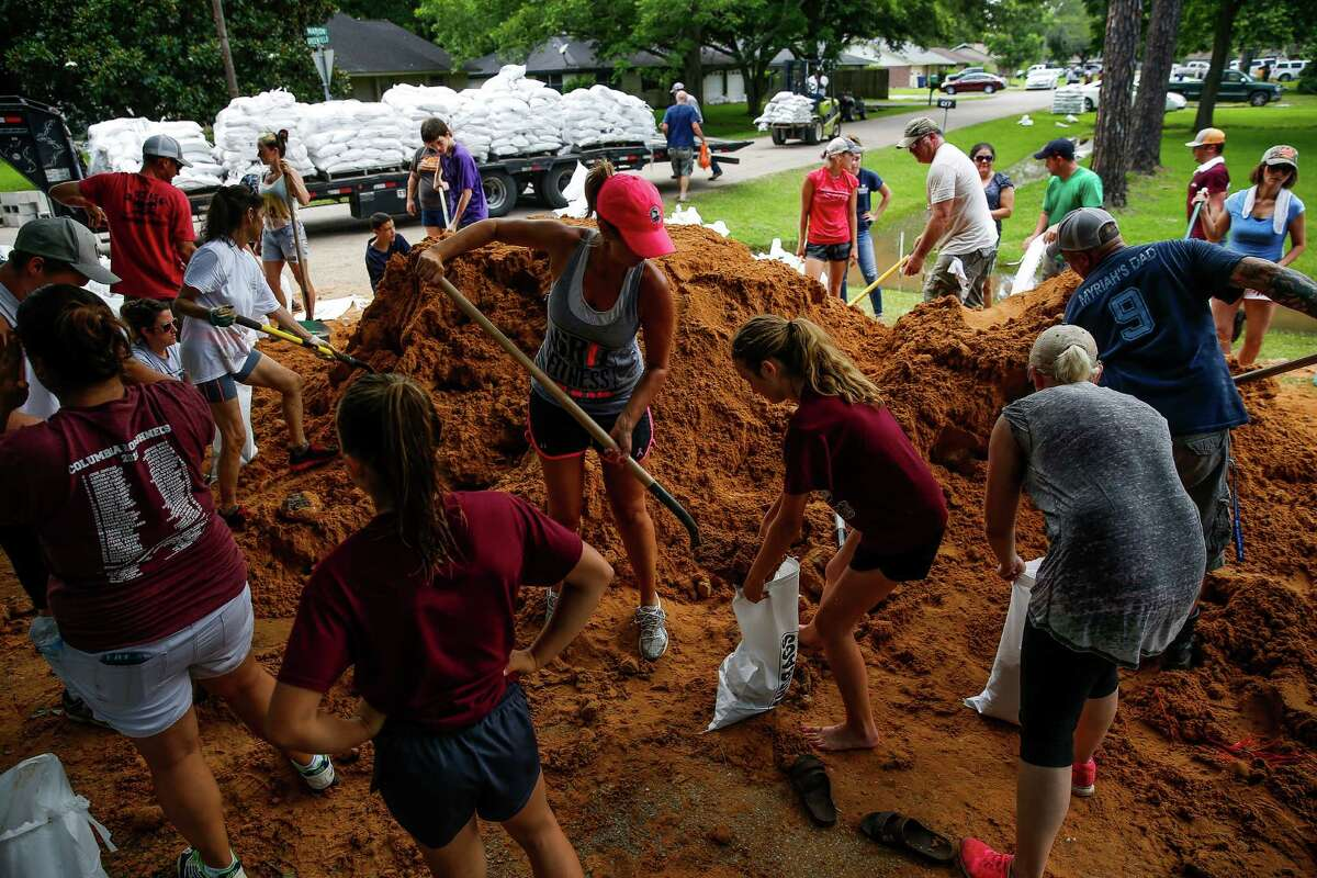 April Kondra, center left, and her daughter, Kate Kondra, 11, help fill sand bags in West Columbia. Community members have rallied together to build thousands of feet of dams to protect the city from flooding.