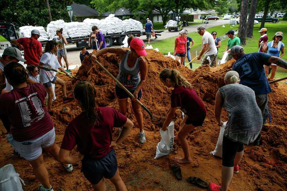 April Kondra, center left, and her daughter, Kate Kondra, 11, help fill sand bags in West Columbia. Community members have rallied together to build thousands of feet of dams to protect the city from flooding.  Photo: Michael Ciaglo, Staff / © 2016  Houston Chronicle