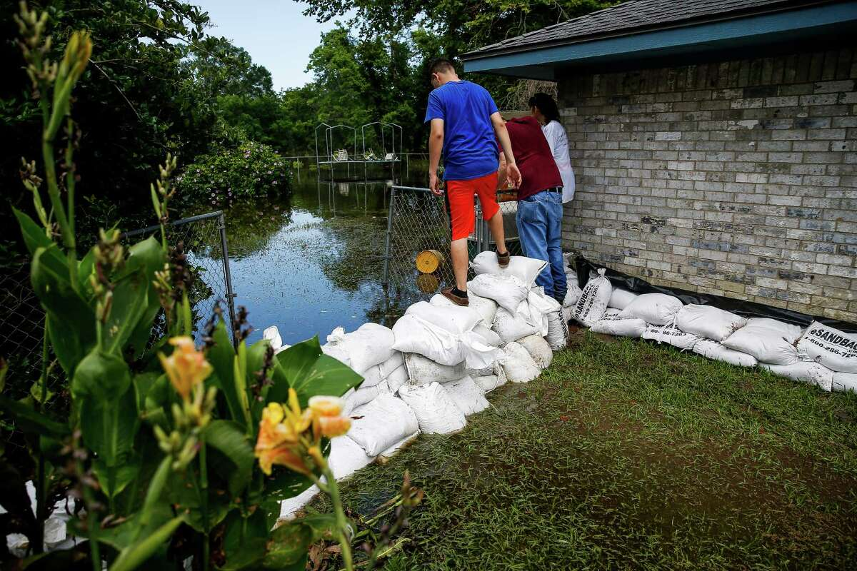 Volunteers check out the rising floodwaters being held back by sandbags. So far, the dams have been holding and have limited damages to minor flooding in a few homes.