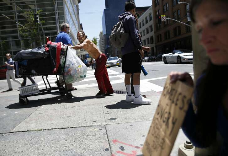 A man pushes a grocery cart across Second Street while Christine Boyer (right) panhandles on the corner of Mission and Second Street on Friday, May, 27, 2016 in San Francisco, California.