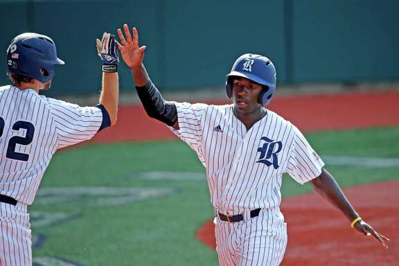 Rice's Ryan Chandler is greeted by Grayson Lewis (22) after he scored during the second inning against LSU in an NCAA college baseball tournament regional game in Baton Rouge, La., Tuesday, June 7, 2016. (AP Photo/Gerald Herbert)
