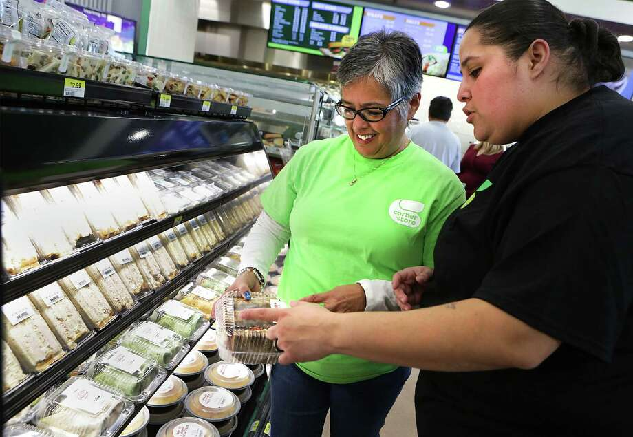 Mary Jean Hernandez, left, listens to Elena Rivera, Food Service Manager of the Corner Store at Zarzamora and 410 as she explains about the fresh sandwiches. The foreign owners of the 7-Eleven chain of mini-marts and Canada's Alimentation Couche-Tard Inc., the parent company for Circle K, have submitted bids for CST Brands Inc., which operates the Corner Store convenience stores. Photo: BOB OWEN /San Antonio Express-News / San Antonio Express-News