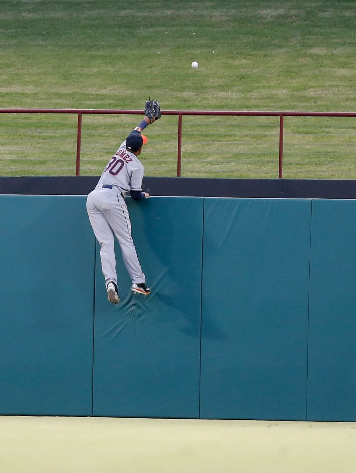 A valiant effort by Astros center fielder Carlos Gomez fails to prevent a home run hit by the Rangers' Bobby Wilson in the fifth inning.