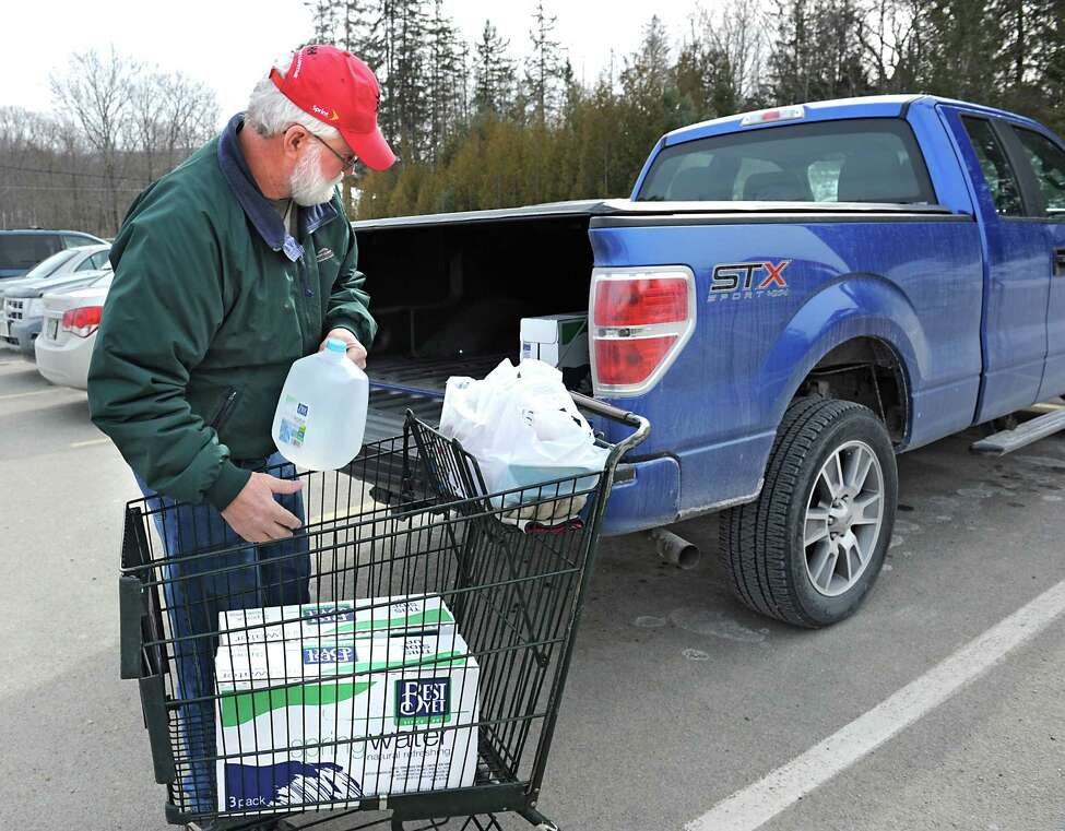 Mike McGuire of Hoosick Falls loads spring water, bought at Tops grocery store, into the back of his pickup truck on Friday, Feb. 12, 2016 in Hoosick Falls, N.Y. McGuire has been a resident of Hoosick Falls for 63 years and worked at Saint-Gobain for 41 years. (Lori Van Buren / Times Union)