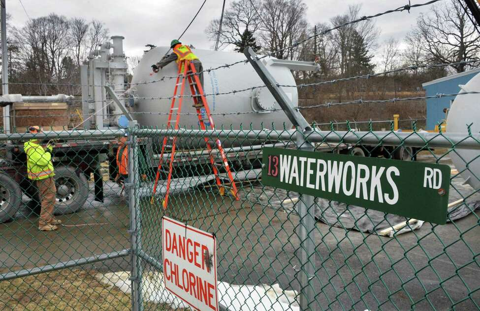 Workers take delivery of a temporary water treatment system Tuesday Jan. 26, 2016 in Hoosick Falls, NY. (John Carl D'Annibale / Times Union)