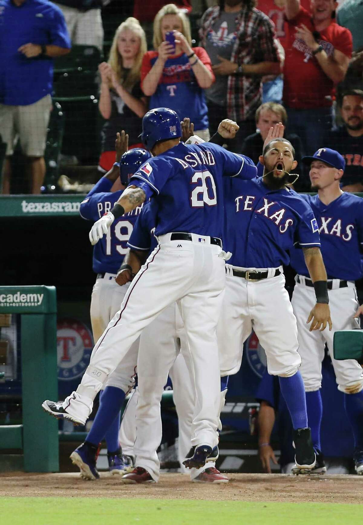 The Rangers' Ian Desmond (20) receives a hearty welcome after hitting a two-run homer in the eighth inning against the Astros.