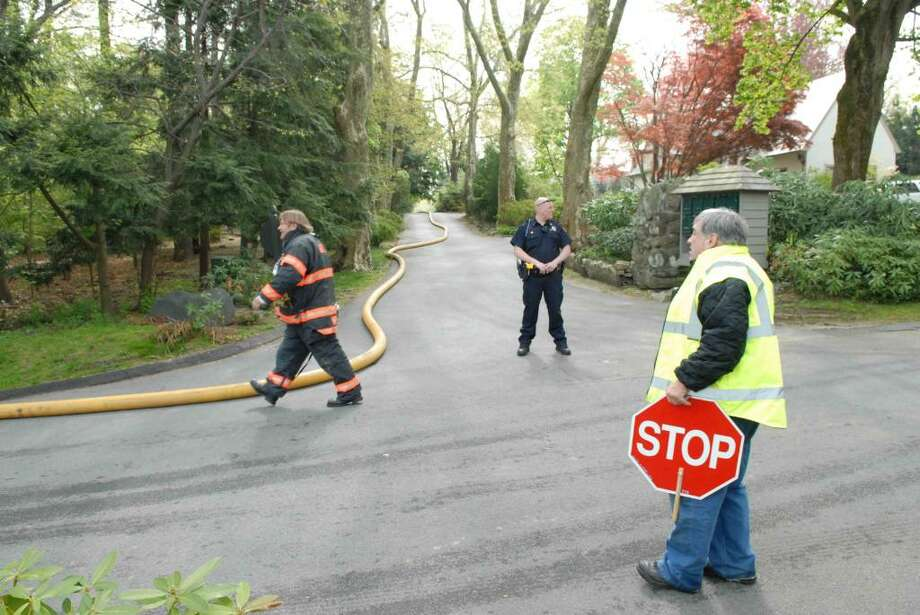 Greenwich fire and police officials near the scene of an attic fire in the private section of Mead Point on Indian Field Road Wednesday morning. Photo by John Ferris Robben. Photo: Contributed Photo / Greenwich Time Contributed