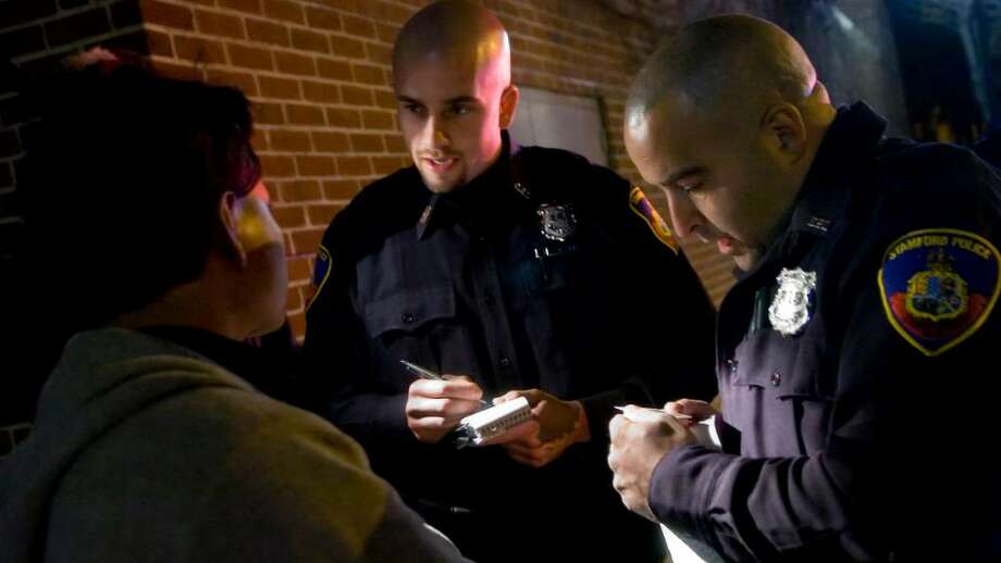 Stamford Police Officer Gregory Zach, center, will be placed on probationary employment status for 18 months and faces additional disciplinary actions after a 2009 incident where he was alleged to have punched a woman at an Alive@Five concert. Photo: File Photo / Stamford Advocate File Photo