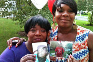 Barbara Smalls, of Norwalk, left, and April Barron of Bridgeport, hold photos of Rickita Smalls and Iroquois Alston, who were shot to death a year ago Monday in Norwalk, during a remembrance ceremony held a the site of the crime.