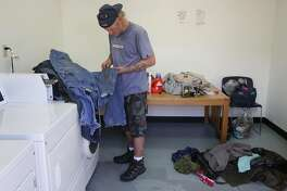 "Pete Kautzmann, 48, checks the lingering stains on his pants while doing laundry with his wife at the Navigation Center homeless shelter June 3, 2016 in San Francisco, Calif. Kautzmann and his wife are considered residents though they obtained an RV right before being admitted into the shelter and have been allowed to sleep in it and use the shelter's services. ""They've been bending over backwards for us."" said Rosie Sullivan, Kautzmann's wife."
