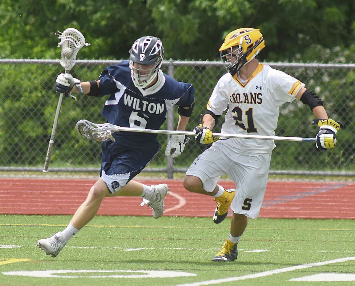 Wilton's Peter Koch, left, protects the ball while being checked by Simsbury's Zachary Magaw during Saturday's Class L boys lacrosse quarterfinal in Simsbury.