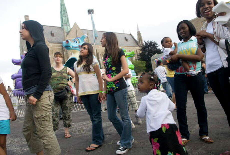 In this June 22, 2008 file photo, Larissa Martins, 12, center left, Karen Escobar, 13, center right, and Seriyah Smith, 3, watch people on a ride during the St. Mary's Fair at St. Mary's Church in Stamford, Conn. This year's fair will be from June 16 through June 19. Chris Preovolos/Staff photo Staff Photo Chris Preovolos Photo: CHRIS PREOVOLOS / ST / 00007220A