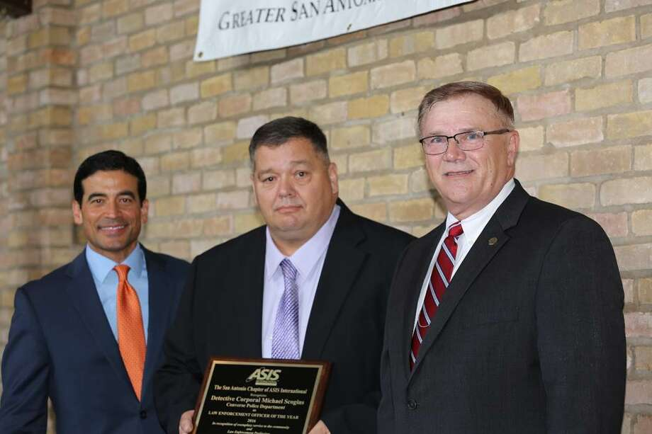 "DA Nico LaHood, Mark Hammargren honor Converse Police Detective Mike Scogins (center) receives his   ""Officer of the Year"" from Nico LaHood, Bexar County District Attorney, left, and Mark Hammargren, AIS-San Antonio chairman, at the organization's May 11 annual awards ceremony. Photo: Courtesy Photo /"